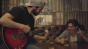 Homem farpado positivo novo que joga a guitarra na barra, seu amigo masculino que senta-se perto de agitar sua cabeça no ritmo vídeos de arquivo