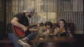 Homem farpado positivo novo que joga a guitarra na barra, seus amigos que sentam-se perto da cerveja bebendo Lazer no bar guys vídeos de arquivo