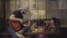 Homem farpado positivo novo que joga a guitarra na barra, seus amigos que sentam-se próximo Lazer no bar Indivíduos e menina que  filme