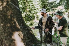 Homem farpado positivo que pesca com seu pai envelhecido imagem de stock