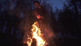 Homem farpado que desbasta um log ardente na noite no indivíduo brutal da floresta com machado fora filme