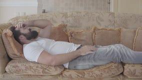Homem farpado que encontra-se no sofá que verifica o telefone celular Beardie está irritado, ele joga afastado o smartphone Receb vídeos de arquivo