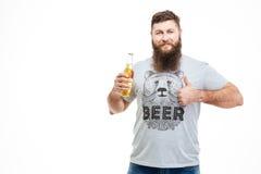 Homem farpado que guarda a garrafa da cerveja e que mostra os polegares acima Foto de Stock Royalty Free