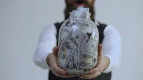 Homem farpado que guarda um frasco completamente do dinheiro isolado no fundo branco Obten??o rico Armazenamento inteligente do d vídeos de arquivo