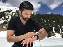 Homem farpado que olha o relógio ao estar a montanha próxima da neve em Canadá Foto de Stock