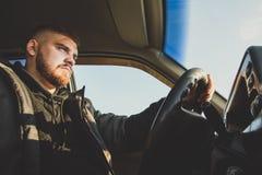 Homem farpado que senta-se atrás da roda do russo fotografia de stock