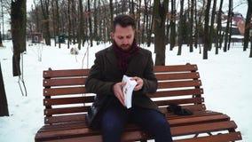 Homem farpado que senta-se no banch no parque do inverno O homem de negócios abre seu caso e obtém o livro filme