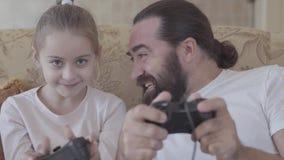 Homem farpado que senta-se no sofá e que joga o manche da terra arrendada do jogo de vídeo com seu fim pequeno da filha acima Con vídeos de arquivo