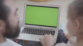 Homem farpado que senta-se no sofá que fala a sua filha pequena ao usar o portátil pequeno, ensinando a trabalhar com video estoque