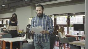 Homem farpado sério concentrado que estuda os documentos de papéis que estão no escritório moderno Duas mulheres que falam no filme