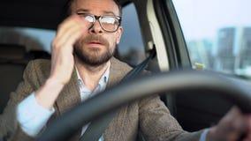 Homem farpado satisfeito nos vidros que conduzem um carro abaixo da rua no tempo ensolarado vídeos de arquivo