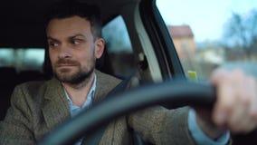 Homem farpado satisfeito que conduz um carro abaixo da rua no tempo ensolarado filme