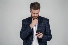 Homem farpado 'sexy' bonito com um corte de cabelo bonito com um telefone em sua m?o O empregado ? copiado seriamente com o chefe foto de stock