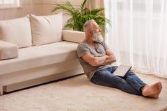 Homem farpado superior pensativo com a tabuleta digital que olha a janela e que senta-se no assoalho fotografia de stock