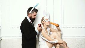 Homem farpado vestido em um terno e em comer uma posição da maçã perto de uma mulher que máscara vestindo do coelho e em comer um video estoque