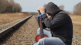 Homem fatigante com a guitarra na estrada de ferro vídeos de arquivo