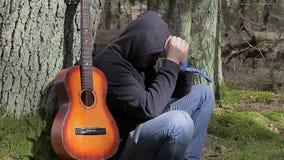 Homem fatigante com a guitarra na floresta vídeos de arquivo