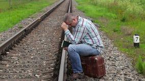Homem fatigante que senta-se na mala de viagem perto da estrada de ferro filme
