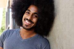 Homem feliz com barba e inclinação afro na parede foto de stock