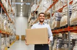 Homem feliz com a caixa do pacote do cartão no armazém Imagens de Stock