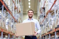 Homem feliz com a caixa do pacote do cartão no armazém Foto de Stock Royalty Free