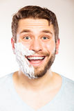 Homem feliz com espuma do creme de rapagem na metade da cara fotos de stock royalty free