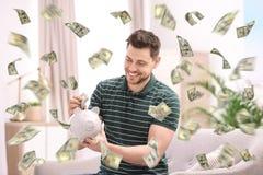 Homem feliz com mealheiro e dinheiro de voo fotos de stock royalty free