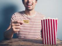 Homem feliz com o bilhete da pipoca e do cinema fotografia de stock