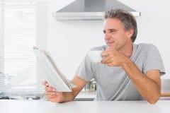 Homem feliz com o jornal da leitura do café imagem de stock