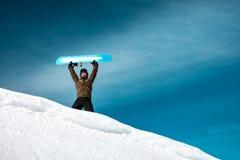 Homem feliz com o snowboard nas montanhas fotos de stock royalty free