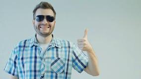 Homem feliz com os óculos de sol que mostram os polegares acima ou para gostar, emoção humana do conceito video estoque