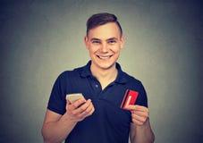 Homem feliz com smartphone e cartão de crédito fotografia de stock royalty free