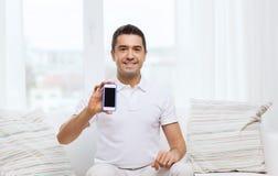 Homem feliz com smartphone em casa fotos de stock royalty free