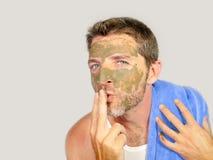 Homem feliz com toalha do banheiro que sorri com creme verde em sua cara que aplica a máscara facial que envia o beijo a sua refl foto de stock royalty free