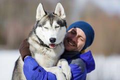 Homem feliz com um cão de puxar trenós Imagens de Stock