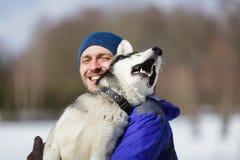 Homem feliz com um cão de puxar trenós Fotos de Stock Royalty Free