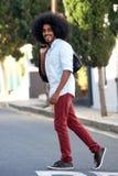 Homem feliz da juventude com passeio afro através da rua fotos de stock