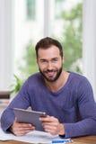 Homem feliz de sorriso que trabalha com uma tabuleta Imagens de Stock Royalty Free