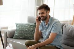 Homem feliz de sorriso que usa o portátil e falando no telefone em casa imagem de stock royalty free