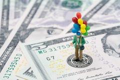 Homem feliz diminuto que guarda balões coloridos no emblema dos E.U. Federal Reserve na cédula dos dólares americanos como FED co imagem de stock royalty free