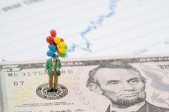 Homem feliz diminuto que guarda balões coloridos no emblema dos E.U. Federal Reserve na cédula dos dólares americanos como FED co fotos de stock