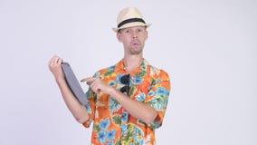 Homem feliz do turista que usa a tabuleta digital e dando os polegares acima video estoque