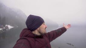 Homem feliz do viajante que toma o selfie e que mostra o lago Ritsa na Abkhásia no inverno vídeos de arquivo