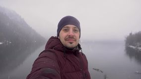 Homem feliz do viajante que toma o selfie no lago Ritsa na Abkhásia no inverno video estoque