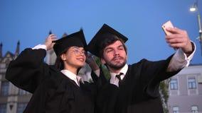 Homem feliz e alunos diplomados fêmeas que tomam um selfie filme
