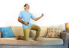 Homem feliz e entusiasmado novo que salta no sofá do sofá que escuta a música com o telefone celular e os fones de ouvido que jog Fotografia de Stock Royalty Free