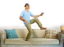 Homem feliz e entusiasmado novo que salta no sofá do sofá que escuta a música com o telefone celular e os fones de ouvido que jog Fotos de Stock