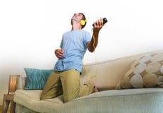 Homem feliz e entusiasmado novo que salta no sofá do sofá que escuta m Fotos de Stock