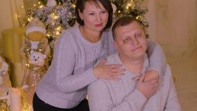 Homem feliz e mulher dos pares que abraçam e que levantam na árvore brilhante do ano novo filme