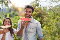 Homem feliz e mulher que comem a melancia junto sobre a terra arrendada tropical bonita de Forest Landscape Cheerful Couple Laugh Fotografia de Stock
